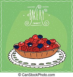 Tartlet with red and blue berries on lacy napkin
