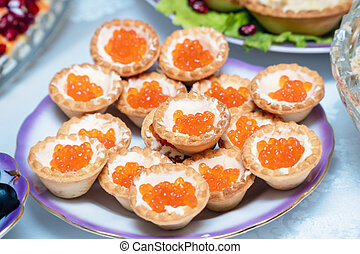 Tartlets with red caviar on a plate.