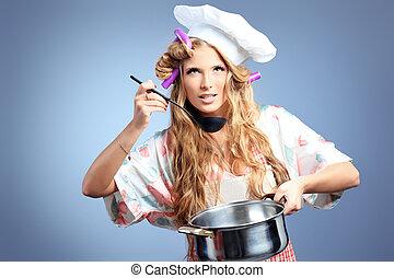 taste - Beautiful blonde woman housewife holding pan. Studio...
