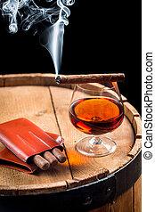 Taste of burnt cigar and cognac