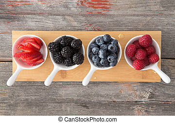 Taster dishes of assorted autumn berries viewed from above...