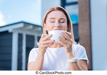 Beautiful mature woman tasting delicious morning cappuccino standing outside