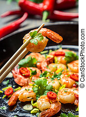 Tasting shrimp with herbs on chopsticks