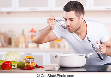 Tasting soup. Handsome young man tasting soup from the pan while standing in the kitchen