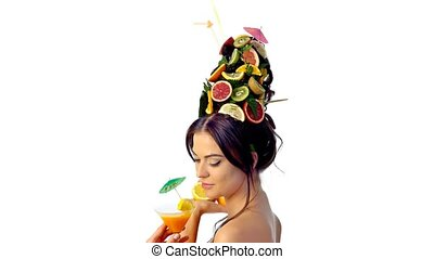 Tasting summer drink by beautiful girl. Drinking martini cocktail in glass. Woman has high hairstyle with fresh fruits as concept summer time.