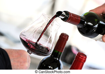 Tasting wine in a vinery-A man's hand is pouring red wine...