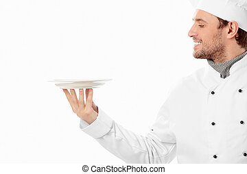 A smiling cook looks at the empty plate on a white background