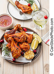 Tasty appetizing baked chicken legs served with spices, rosemary and cranberries on wooden background table. Christmas dish. Copy space.