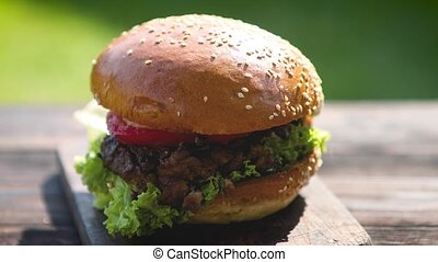 Tasty beef burger with, lettuce, onion and tomatoes served...