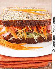 Tasty open sandwich with cucumber relish, smoked beef pastrami and sliced carrots on wholewheat bread