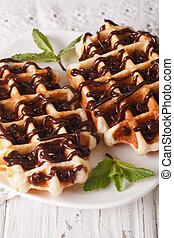 Tasty Belgian waffles with chocolate topping on a plate ...