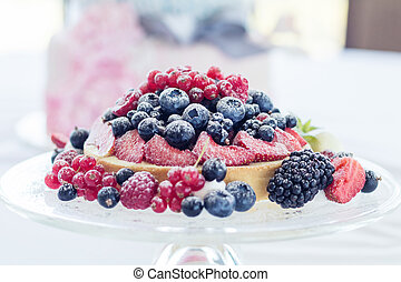 Tasty berry pie with fresh berries on a glass plate. Light background. Shallow depth of field