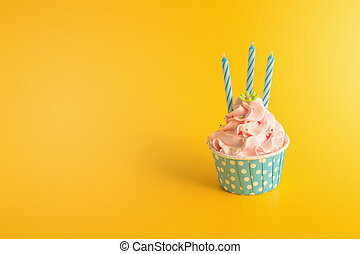 Tasty Birthday cupcake with candles on yellow color background
