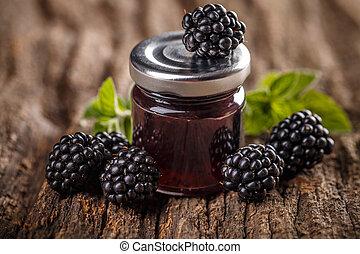 Tasty blackberry jam and fresh berries, on wooden table