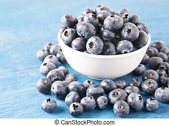 Tasty blueberries in white bowl on a blue wooden table