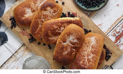 Tasty homemade blueberry bun stuffed with fresh forrest fruits. Traditional polish bun called jagodzianka. Placed on wooden chopping board. Top view, flat lay.