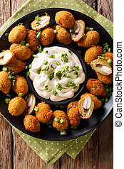 Tasty breaded fried olives with almonds close-up and creamy...