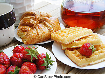Tasty breakfast - tea, croissants, wafers with cream and ...