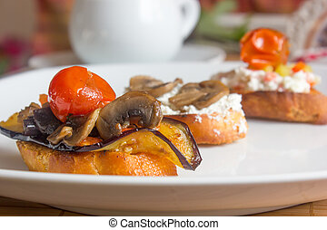 Tasty bruschetta with the eggplants, mushrooms, cherry tomato and sweet pepper.