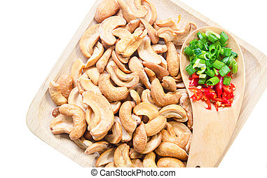 Tasty cashew nuts with red chilli in wooden plate.