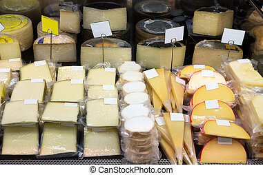 Tasty cheese in packs and in bulk on counter at store
