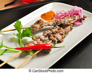 Chinese beef skewer on a white plate