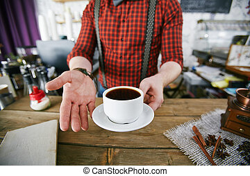 Tasty coffee - Barman holding cup of black coffee over...