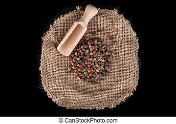 Tasty colorful pepper on jute material. Fresh spices used in home cooking.