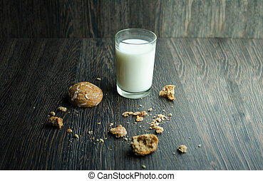 Tasty cookies and glass of milk on wooden background