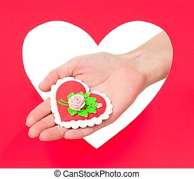 Tasty cooky in the form of heart on a woman palm against red heart