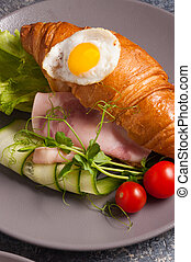 croissant with ham, cucumber and egg. Concept: Breakfast