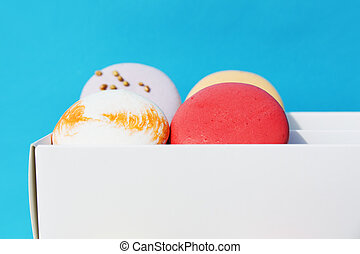 Tasty different colored macarons in white box on blue background