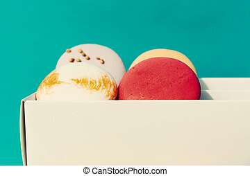 Tasty different colored macarons in white box on blue background.