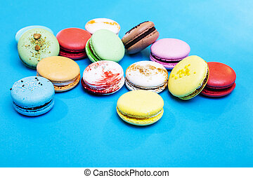 Tasty different colored macarons on blue background