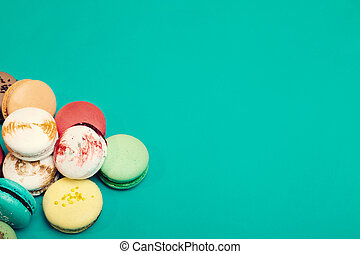 Tasty different colored macarons on blue background.