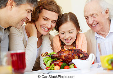 Tasty dish - Family of four around roasted chicken in...