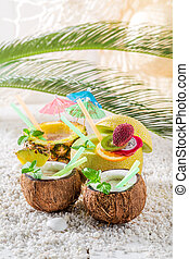 Tasty drinks in fresh fruits with cocktail umbrellas