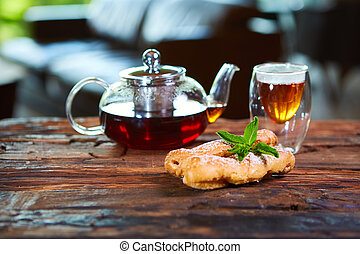 Tasty eclair and cup of tea on wooden table