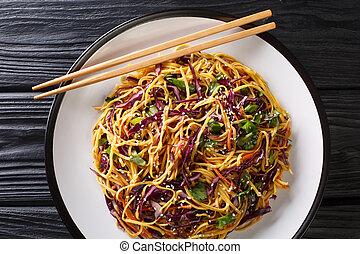 Tasty egg noodles with vegetables and sesame seeds close-up ...
