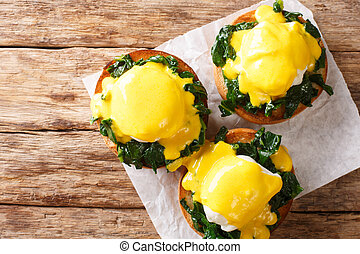 Tasty Eggs Benedict with spinach and hollandaise sauce on a ...
