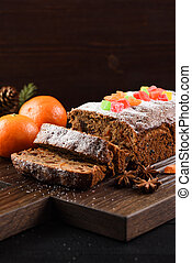 Tasty English fruit cake decorated with candied fruits served with clementines on oak board copyspace