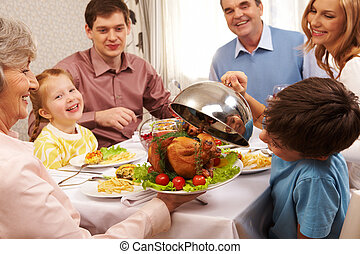 Portrait of happy family sitting at festive table and holding each other by hands
