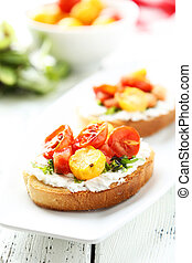 Tasty fresh bruschetta with tomatoes on plate on white wooden background