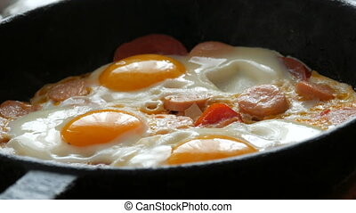 Tasty fresh fried eggs in a vintage cast-iron frying pan, ...