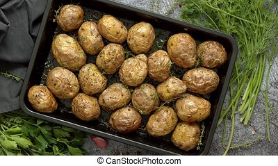 Tasty fresh homemade baked potatoes served on a metal tray. ...