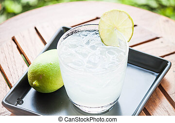 Tasty fresh lime juice with lime on wood table