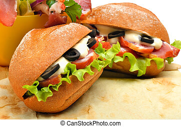 Tasty fresh sandwiches with green lettuce, ham and olives on lav