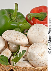 Tasty fresh white mushrooms and peppers in a basket