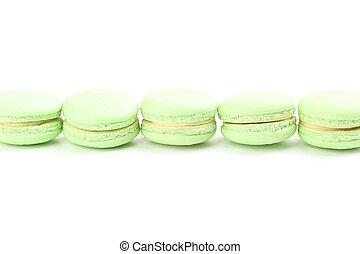 Tasty green macarons on white background
