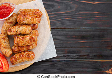 Tasty grilled sausage on the wooden background. Top view with copy space